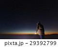 Silhouette of a man with a flashlight, observing 29392799