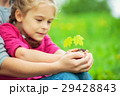 Adult and child holding little green plant in 29428843