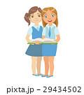 Two Girls In School Uniform Standing Reading A 29434502
