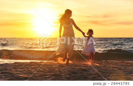 happy family  mother and daughter run, laugh and play at beach 29443795