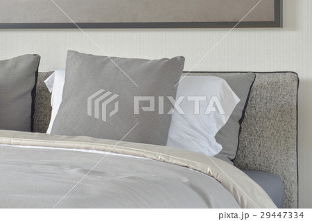 gray and white pillows setting on bed 29447334