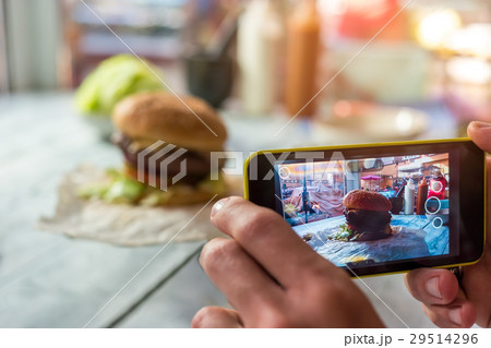 Cell phone photographing a burger. 29514296