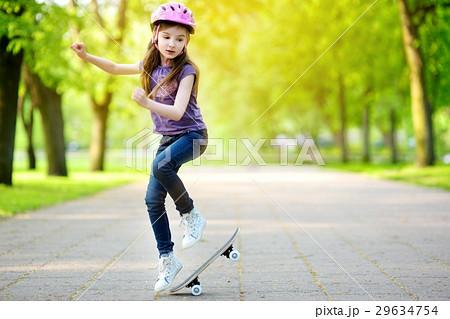 Pretty little girl learning to skateboard outdoors 29634754