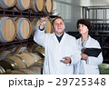 Worker of winery holds glass of red wine in hand and shows him to expert 29725348