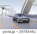 高速道路に走っているシルバー色の自動車。後ろに吊下げ式モノレールがある 29785461