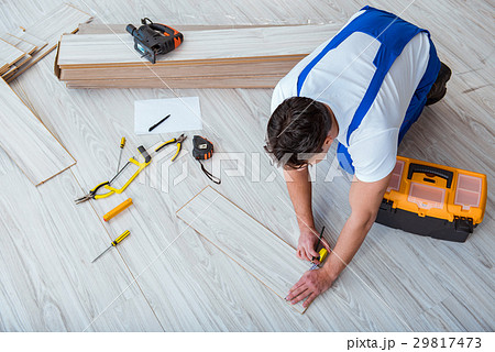 repairman laying laminate flooring at home 29817473. Black Bedroom Furniture Sets. Home Design Ideas