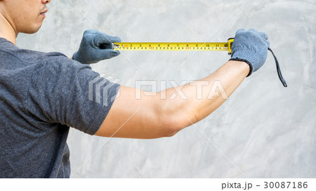 Man wear a glove and holding a measuring tape. 30087186