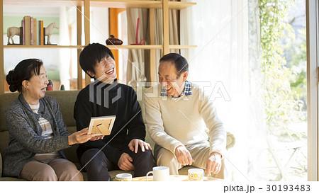 祖父母と写真を見る孫 30193483
