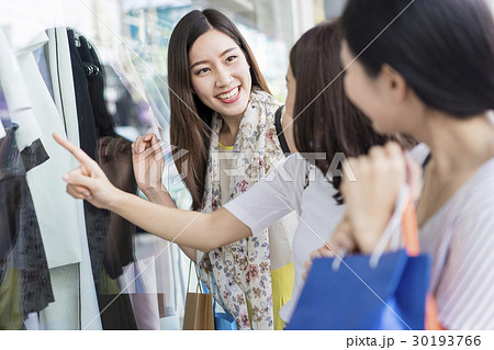 a group of women window shopping in shopping mall の写真素材