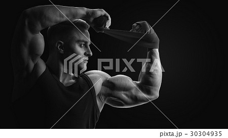 Man is wrapping hands with boxing wraps 30304935
