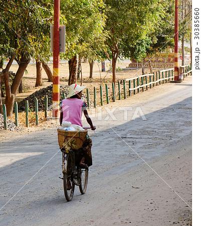 Burmese people biking on rural road in Baganの写真素材 [30385660] - PIXTA