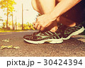 Male jogger tying his running shoes 30424394