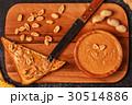 Bowl of peanut butter on wooden board. 30514886