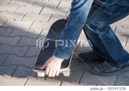 boy learns to ride a skateboard 30545326