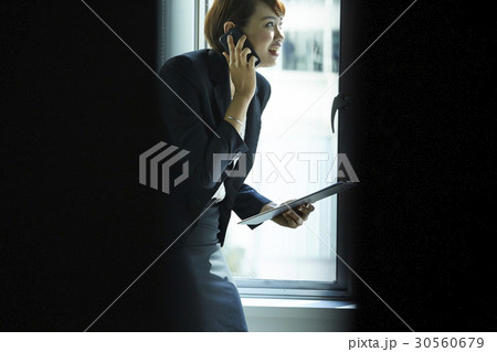 A smiling businesswoman is talking on phone and holding files. 30560679