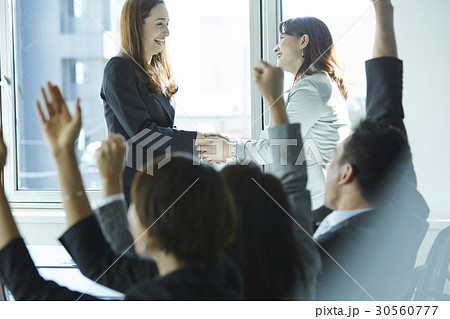two women smiling and shaking hand with a cheer from othersの写真