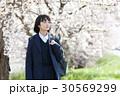 制服を着て桜の木の前に立つ女子高生 30569299