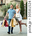 Young couple carrying few paper bags outdoors 30581524