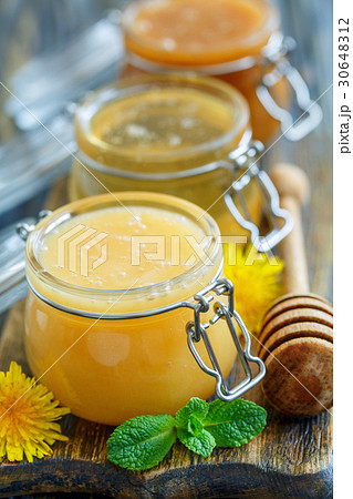 Different varieties of honey in glass jars. 30648312
