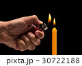 Hand holding burning gas lighter to light candle. Studio shot isolated on black background 30722188