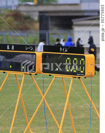 雨の陸上競技場とタイム計測器 30775605