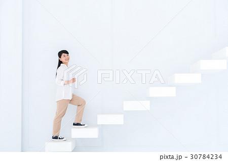 階段を上る若い女性の写真素材 [...