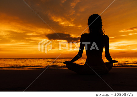 silhouetted woman in lotus pose on backgroundの写真素材