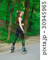 Sports girl in the park on roller skates 30945965