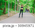 Sports girl in the park on roller skates 30945971