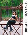 Sports girl in the park on roller skates 30946010