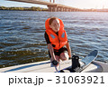 Young fit woman ready to ride water skis siting on 31063921