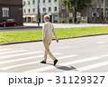 senior man walking along city crosswalk 31129327