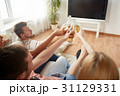 friends clinking beer and watching tv at home 31129331