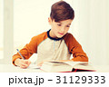 student boy with book writing to notebook at home 31129333