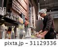 man or barman cooking smoothie at vegan cafe 31129336
