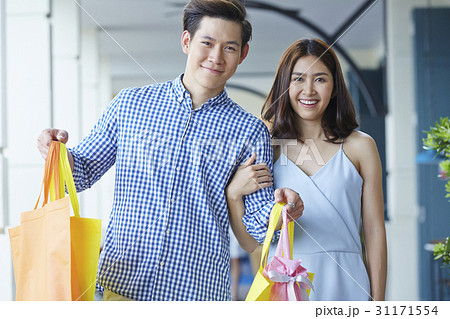 A photo of a lovely couple with bags smiling. 31171554