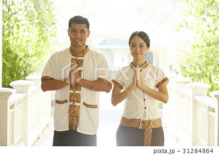 hotel staff smile and welcome guests with hands put together の写真