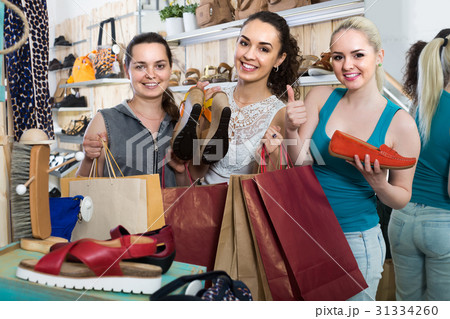three girls holding a paper shopping bags in the boutiqueの写真素材 [31334260] - PIXTA