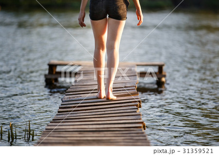 Girl strolling along a pier on pond on sunset 31359521