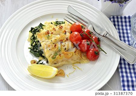 鱈(タラ)のロースト、レモンとガーリックのバター風味 ブルガー小麦とほうれん草のソテー添え 31387370