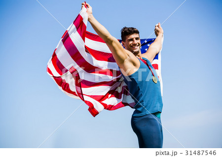Athlete posing with american flag and gold medals around his neck 31487546