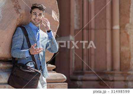 Cheerful smiling male person speaking on phone 31498599