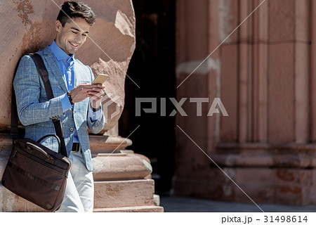 Merry smiling man typing on phone 31498614