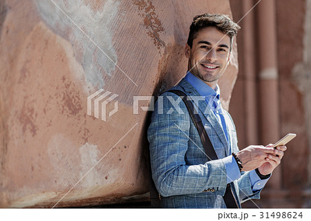 Jolly smiling male person holding phone 31498624