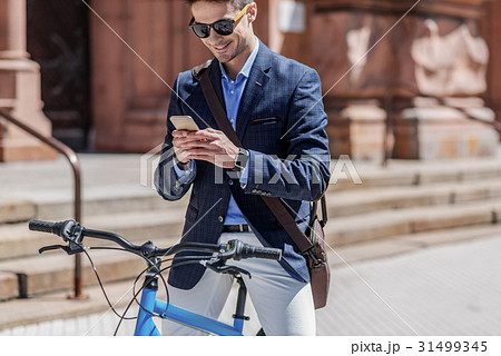 Happy smiling male person using phone 31499345