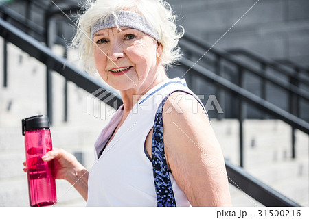 Happy senior woman rising up concrete stairs 31500216