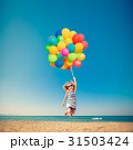 Happy child jumping with colorful balloons on sandy beach 31503424
