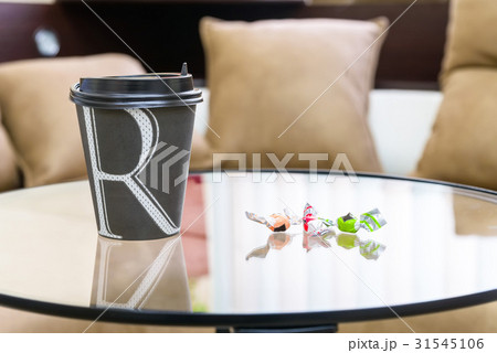 Paper cup of coffee on table with two candiesの写真素材 [31545106] - PIXTA