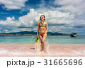 Beautiful young woman holding snorkeling equipment 31665696