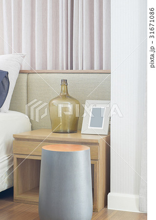 Round shape wooden stool next to bedside tableの写真素材 [31671086] - PIXTA